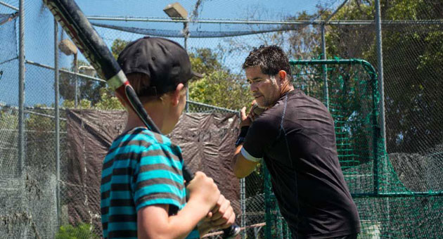 <p>Orlando Guerra coaches a young player, imparting both baseball skills and life lessons.</p>