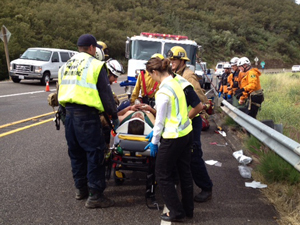 One of two people injured Monday when their vehicle plunged 200 down a steep hillside off Highway 154 is prepared for transport to the hospital. (Ryan Carmel / KEYT News photo)