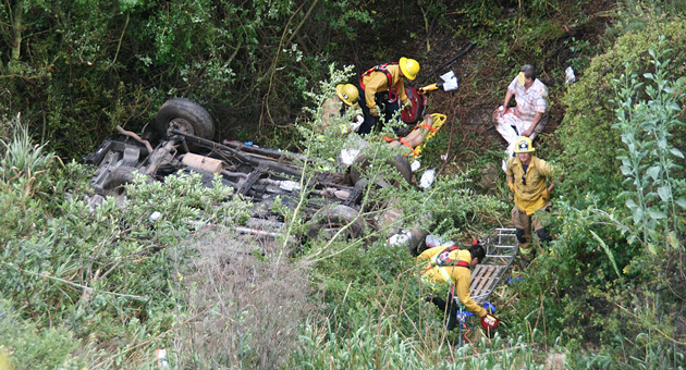 Emergency workers assist the victims of a May 6 car crash on Highway 154 near Santa Barbara. The couple's SUV drove off the side of the roadway and landed on its roof about 200 feet down the mountainside. (Santa Barbara County Fire Department photo)