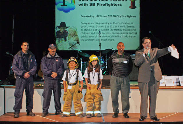 Firefighters and Boys & Girls Club member stand on stage for the live auction, which included a firehouse party for eight kids and their parents with Santa Barbara firefighters at Station 1 at 121 W. Carrillo St. or Station 8 at the Santa Barbara Airport.