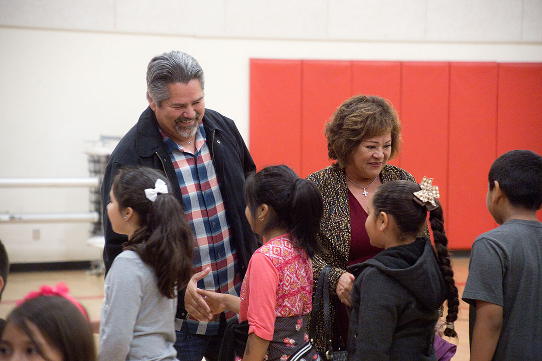 Santa Ynez Band of Chumash Business Committee members Gary Pace and Maxine Littlejohn shake hands with Solvang School students.