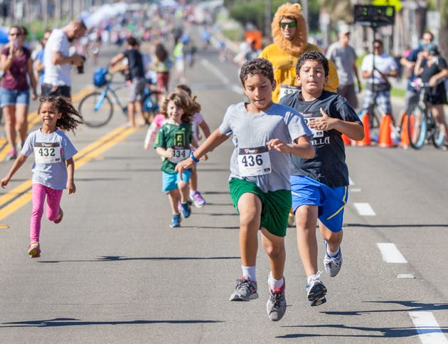 Children sprint to the finish line during a true street race at Santa Barbara's second annual Open Streets festival along East Cabrillo Boulevard.