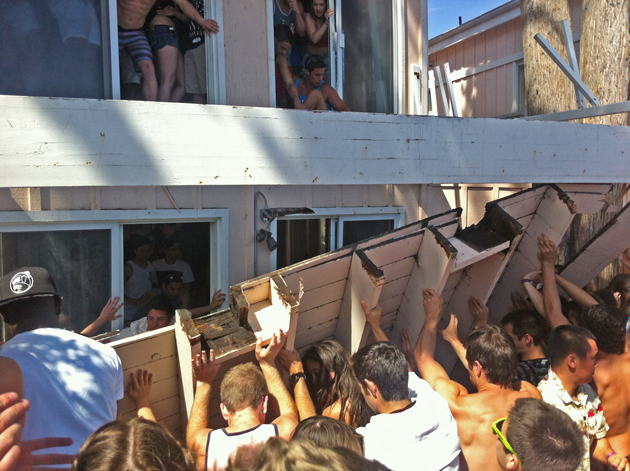 Partygoers work to lift a balcony off people who were injured when the wooden porch collapsed on them during the April 6 'Deltopia' street party in Isla Vista. UC Santa Barbara senior Stephanie Grace suffered a broken pelvis in the incident and has filed a lawsuit against the property's owners and managers. (Robert Clayton photo)
