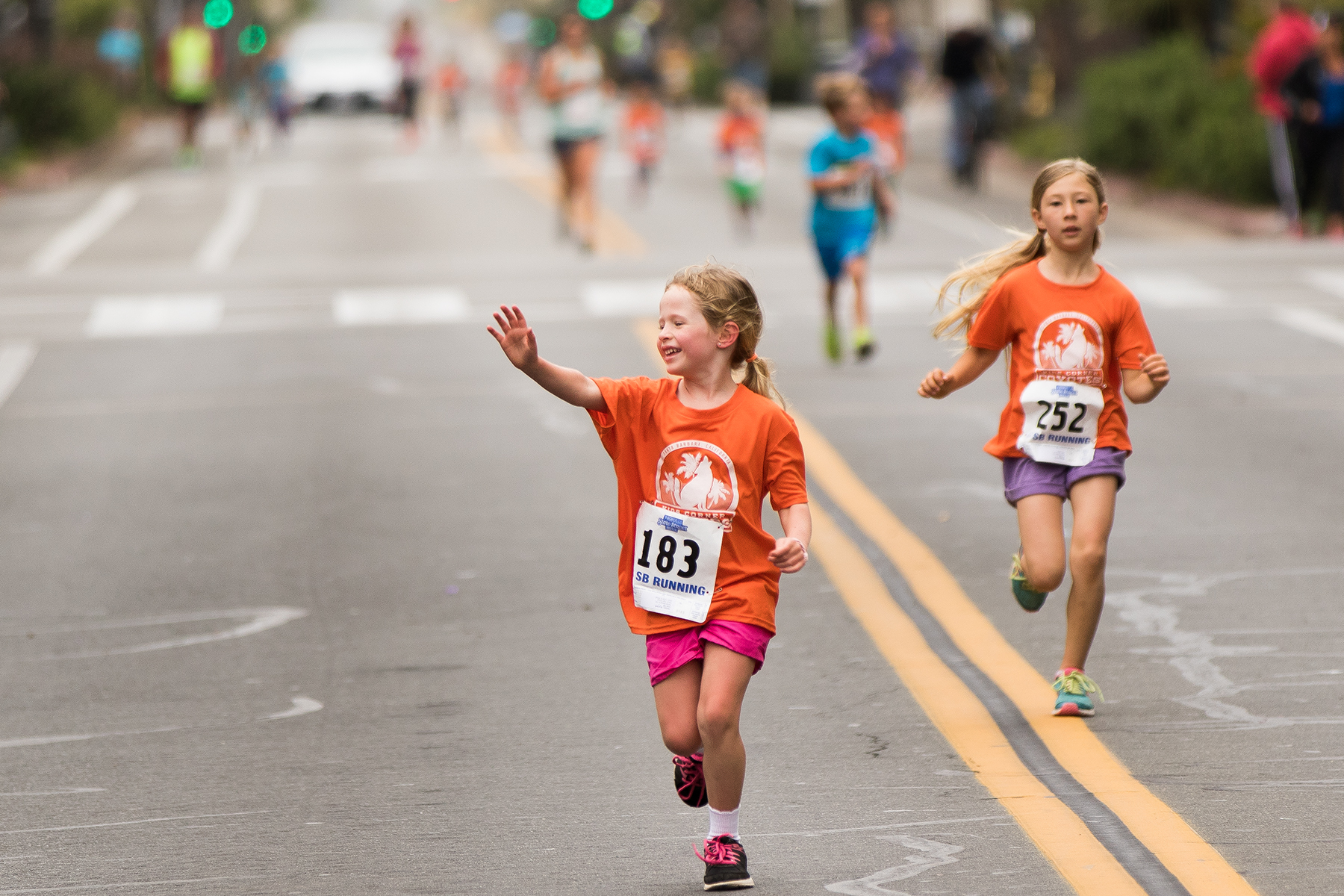 Scarlett Holian, 5, waives to the crowd during the 10/under age race on Saturday morning.
