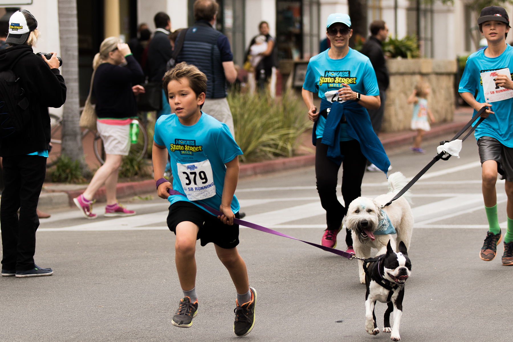 Jack Drown, 9, of Santa Barbara runs with his dog during the State Street Mile on Saturday morning.