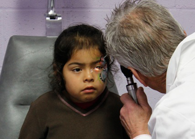 Dr. Barry Mast examines Alessandra Alcocer, 6, during the Kids' Day event at the Santa Barbara Eyeglass Factory on Sunday. (Gabriella Slabiak / Noozhawk photo)