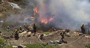 """Firefighters attack flames from the Lookout Fire that were threatening homes in the Painted Cave area. Residents said it was a """"miracle"""" their homes were spared. (Alissa Sears photo)"""