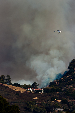 A water-dropping helicopter passes over the Lookout Fire, which has charred 44 acres in the Painted Cave area, threatening homes and forcing evacuations. (Fritz Olenberger photo)