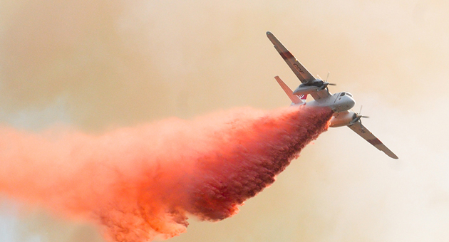 An aerial tanker drops a load of retardant on the Lookout Fire, which charred 44 acres and threatened homes in Painted Cave on Oct. 17, 2012. (Lara Cooper / Noozhawk photo)