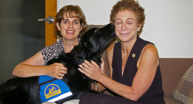 Malvern, a service dog trained to work with victims and witnesses, gives a big kiss to Santa Barbara County District Attorney Joyce Dudley. With them is Donna Crawford, Malvern's owner and handler. (Tom Bolton / Noozhawk photo)