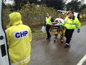 A woman who was injured Friday in a rollover accident on Highway 101 near Milpas Street in Santa Barbara is wheeled to an ambulance for transport to the hospital. (John Palminteri / KEYT News photo)
