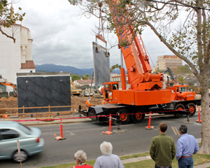 Sections of a historic mural that once adorned the Victoria Street side of the Vons supermarket are relocated to the Chapala Street side of the property on Tuesday to make room for new development. (Alex Kacik / Noozhawk photo)