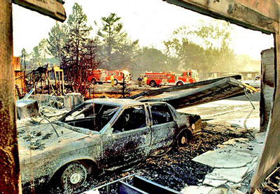 A charred car sits outside a burned-out home after the Painted Cave Fire swept through the area on July 27, 1990. (Keith Cullom file photo)