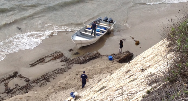 Authorities examine a panga boat and its contents near Gaviota on Wednesday. Eleven people were arrested and 3,000 pounds of marijuana were seized. (Victoria Sanchez / KEYT News photo)