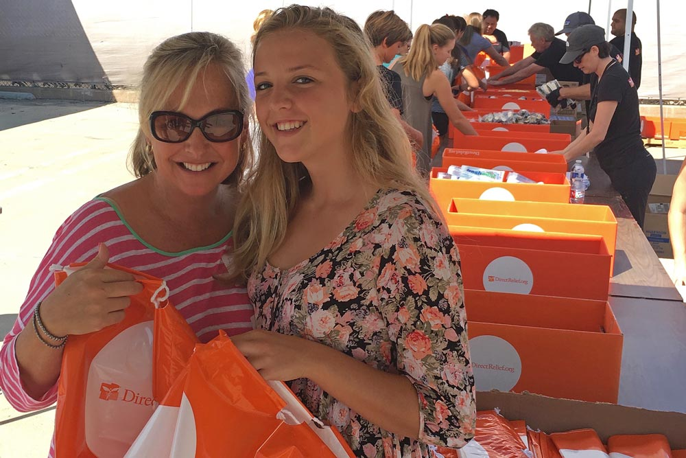 Rachael Steidl and her daughter, Emily, 14, volunteer to help assemble toiletry kits at a Direct Relief packing event.