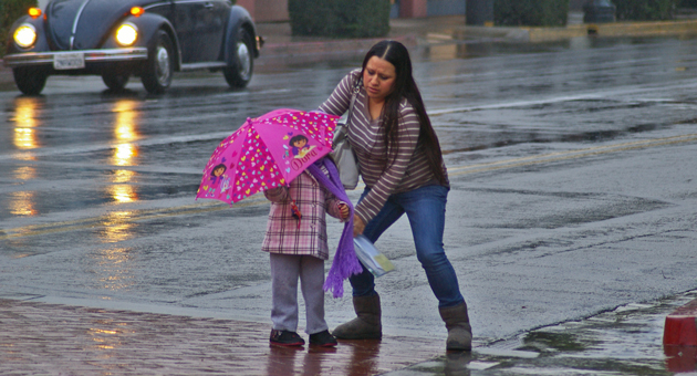 <p>A woman prepares to help a young girl get across a stream of water running down the gutter Wednesday afternoon on Chapala Street in downtown Santa Barbara.</p>
