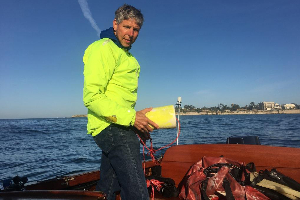 Bob Kiel prepares to set buoys before diving into Goleta Bay.