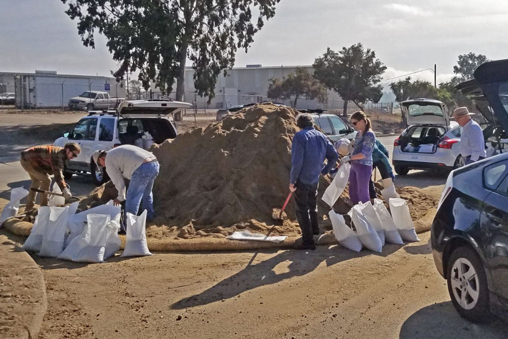 Residents fill sandbags in advance of a powerful storm expected to hit Santa Barbara County on Monday night and Tuesday. Mandatory evacuations have been ordered effective at noon Monday for areas below the Thomas and Whittier burn areas
