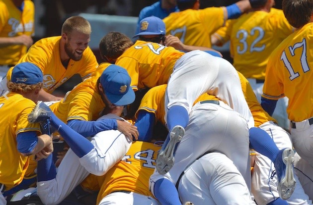 UCSB players pile onto freshman Sam Cohen following his walk-off grand slam, which gave the Gauchos a 4-3 victory over Louisville and a trip to the program's first College World Series.