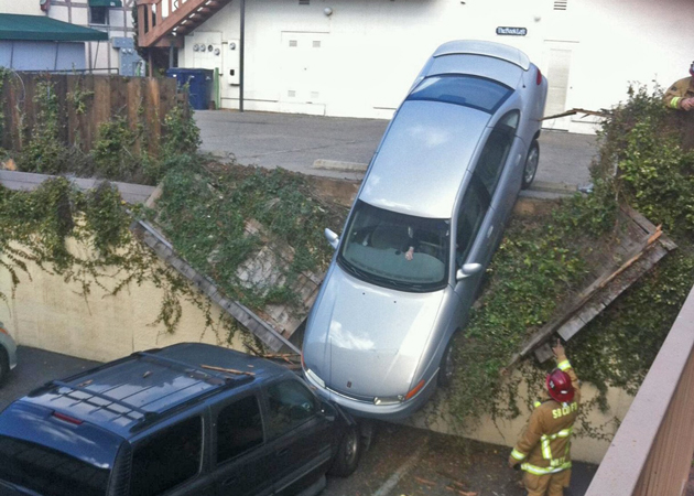 A car sit precariously on another vehicle Thursday after a mishap at a Solvang parking lot. (Adam Estabrook photo)
