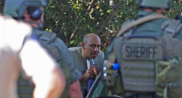 Sheriff's deputies look on as a suicidal man holds a knife to his own throat Wednesday in Montecito. (Harry Rabin photo)