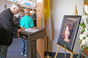 A mourner signs the guest book Friday at Alexandra Tang's funeral at Saint Raphael Church. (Tom Bolton / Noozhawk photo)