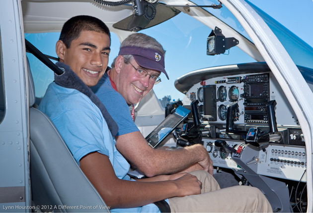 <p>Carl Hopkins, president of the Santa Barbara Experimental Aircraft Association, takes a teen on his first-ever flight in a small plane Saturday during an event sponsored by the nonprofit group A Different Point of View.</p>