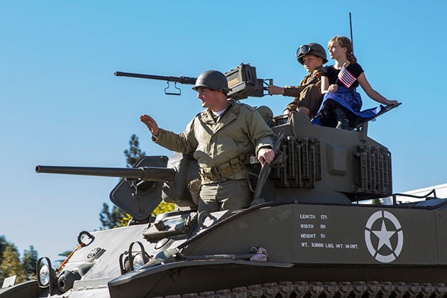 <p>An Army tank rolls down State Street during Sunday&#8217;s Veterans Day Parade with a veteran and a couple of young recruits along for the ride.</p>