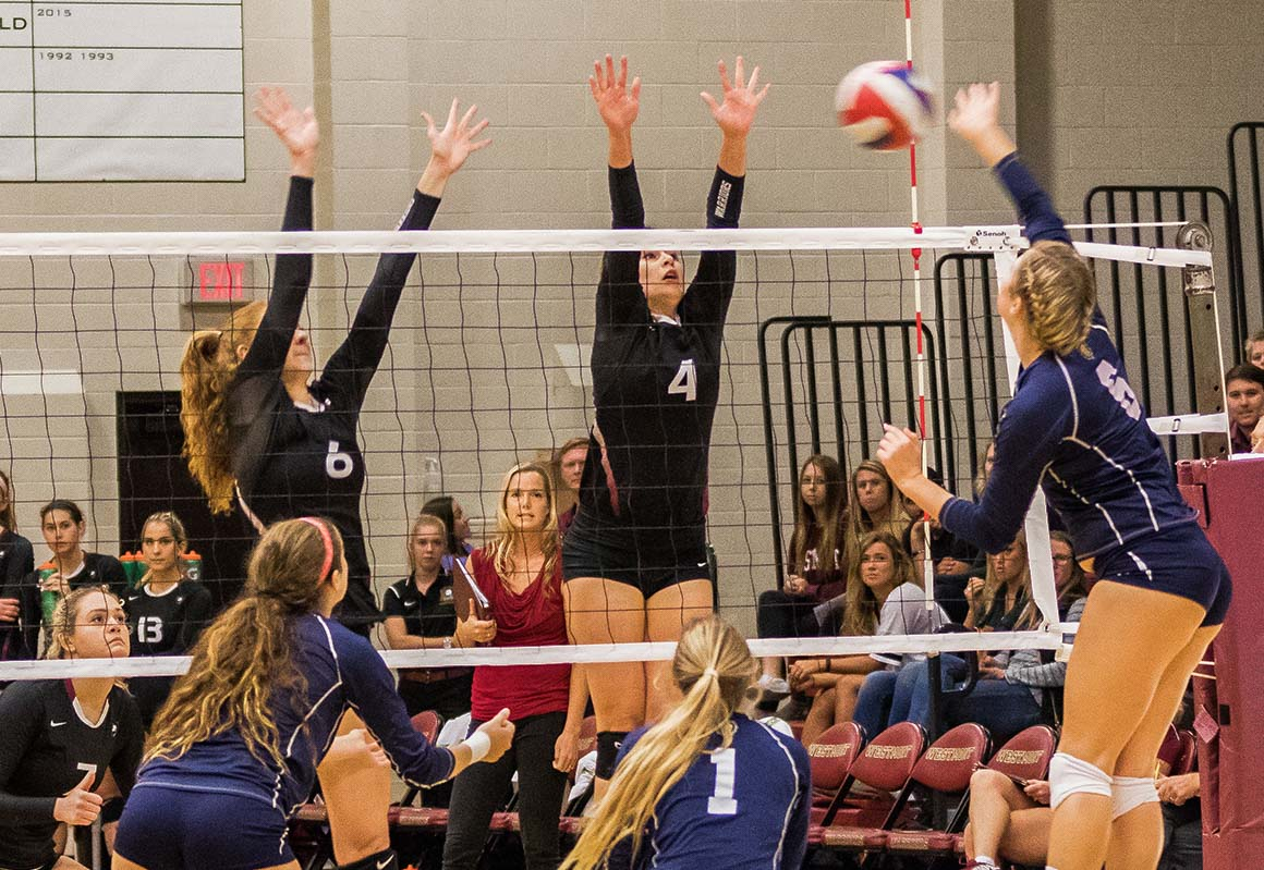 Westmont's Libby Dahlberg (left) and Jessica McCann (right) attempt to block a Vanguard kill