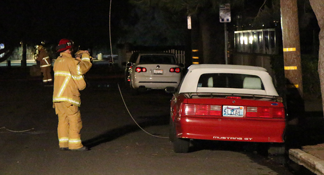 A Santa Barbara city firefighter inspects a dangling power line that was related to an outage Sunday night near West Beach. (John Palminteri / KEYT News photo)