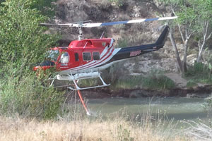 A firefighting helicopter picks up a load of water from the Santa Ynez River while battling the 1,800-acre White Fire along Paradise Road in the Upper Santa Ynez Recreation Area. (Giana Magnoli / Noozhawk photo)