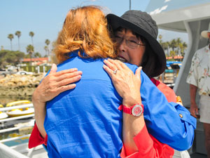 Capt. Fred Benko's widow, Hiroko, hugs a well-wisher Friday as the Condor Express returns to the Santa Barbara Harbor after being repaired. (Lara Cooper / Noozhawk photo)