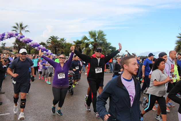 Claire Scholl and Oscar Flores from KEYT raise their arms in support at the start of the race.
