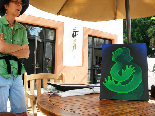 Artist Lesley Gorgan displays one of her paintings on the patio of the Mental Health Association's Fellowship Club Recovery Learning Center.