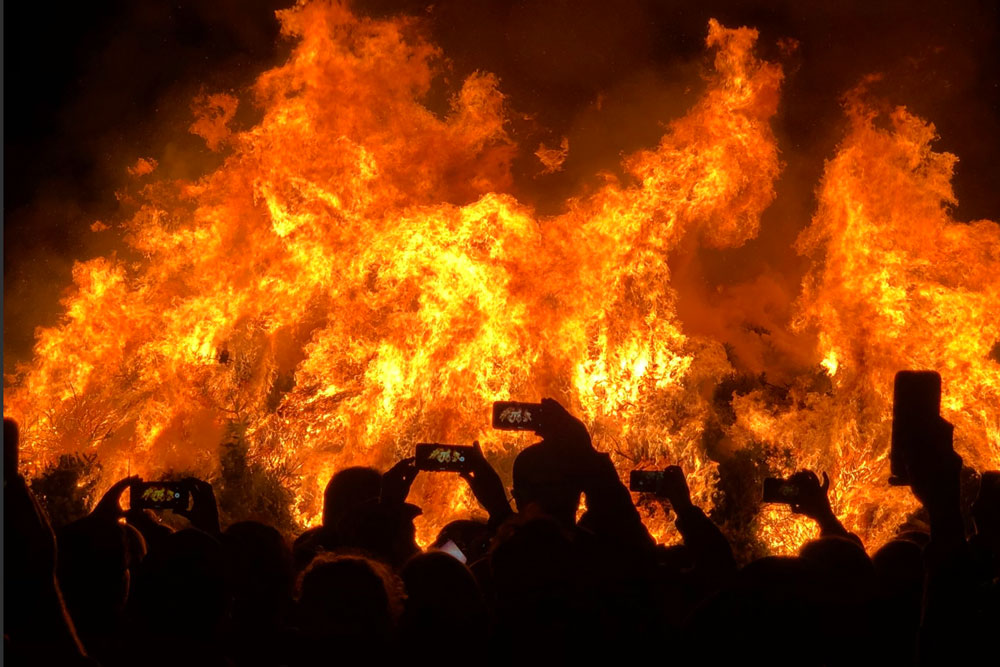 Attendees at the annual Christmas tree burn at Mission Santa Ines in Solvang Friday night use their cell phones to capture the action.