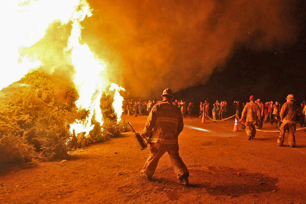 Firefighters set flame to a huge pile of Christmas trees at Mission Santa Ines in Solvang Friday night, culminating the community's annual Julefest celebration.