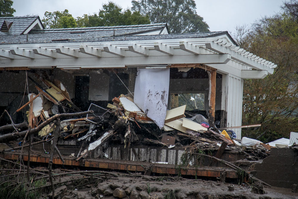 Debris is piled up around a home in Montecito after Tuesday's flash flooding.