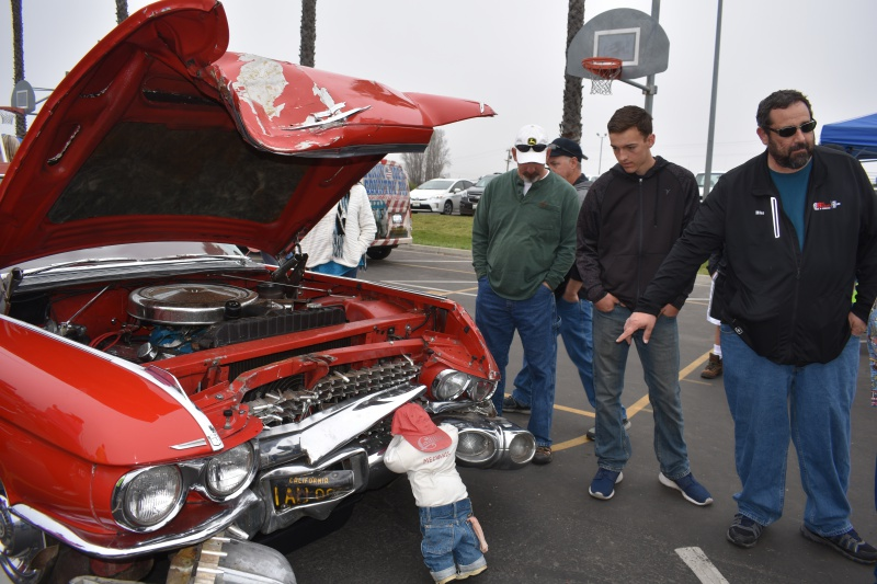 Chad Shuffield, ;eft, grandson of classic car owner John Shuffield, carries on a conversation while standing near the 1959 Cadillac convertible damaged in a crash in Orcutt.