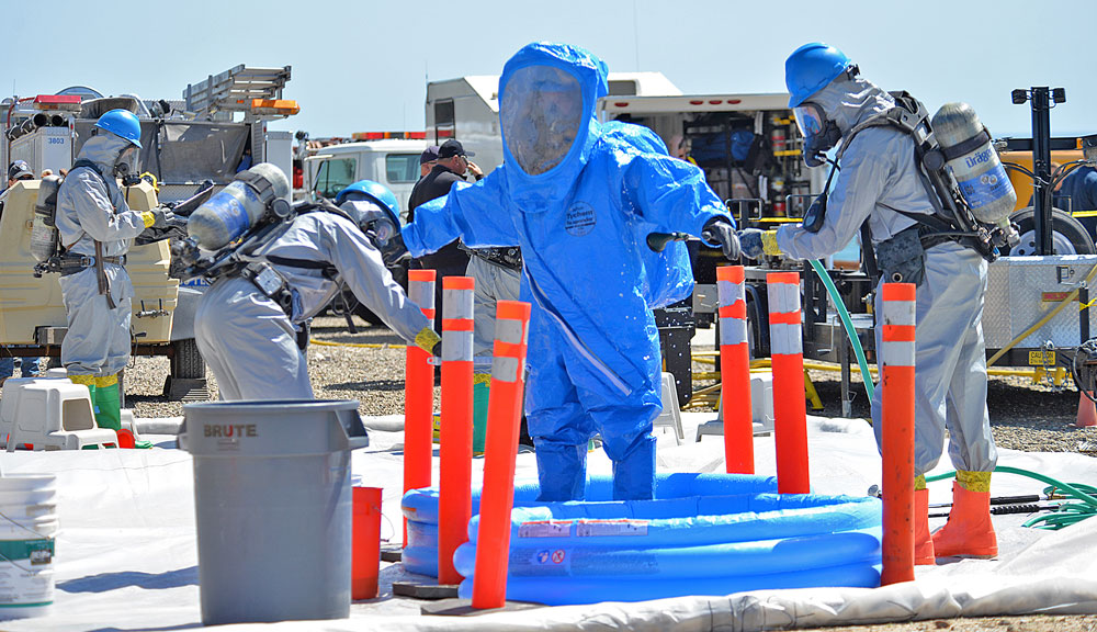 An emergency worker in aspecialized protective suit goes through decontamination Thursday during a multi-agency disaster drill.