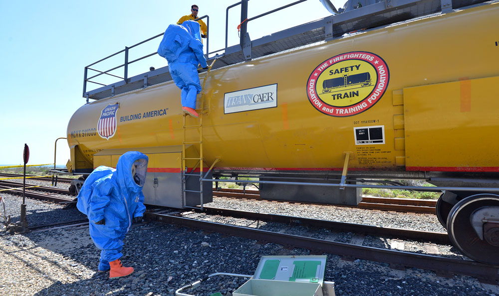 Emergency personnel in specialized protective suits climb up onto a railroad car 'leaking' a hazardous material Thursday during a multi-agency disaster drill.
