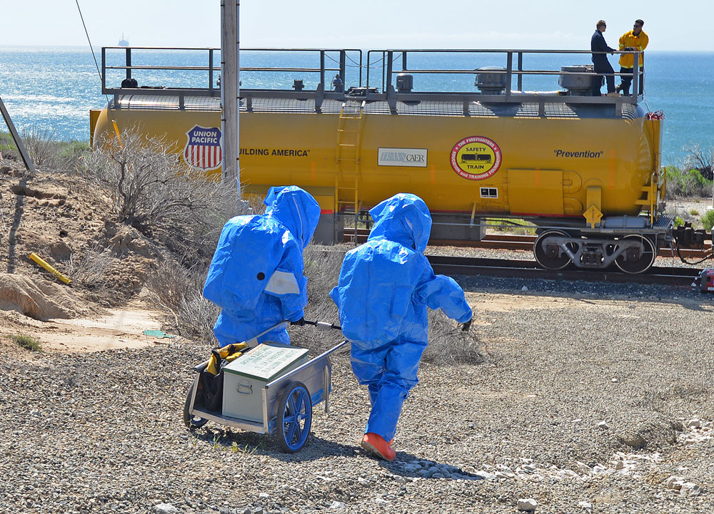 Emergency personnel carry equipment to a railroad car 'leaking' a hazardous material Thursday during a multi-agency disaster drill.
