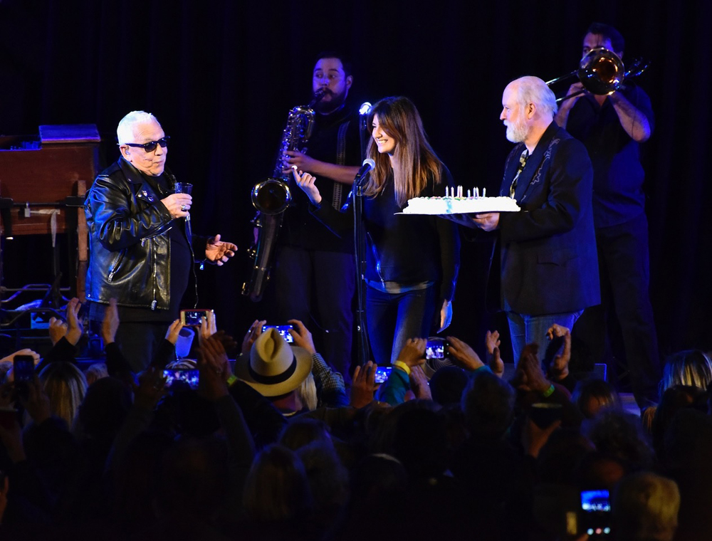 Eric Burdon's wife, Marianna, surprises him on stage with a birthday cake.