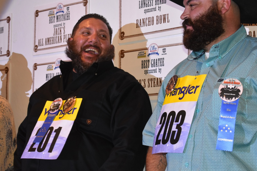 Wildest beard contestant Tommy Barrios, left, shares a laugh with a fellow entrant.