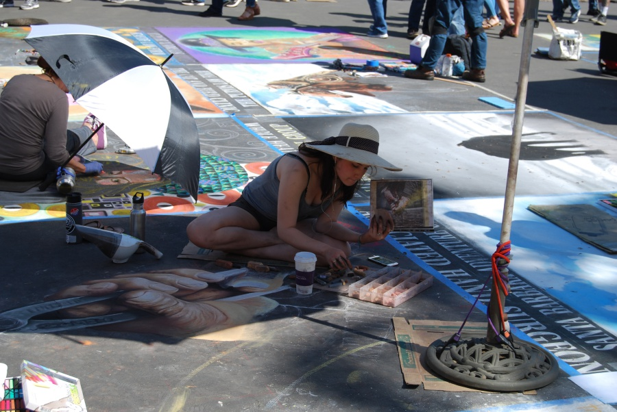 Artist Yuliana Salazar, 22, sketches her chalk piece sponsored by the Associated Hand Surgeons.