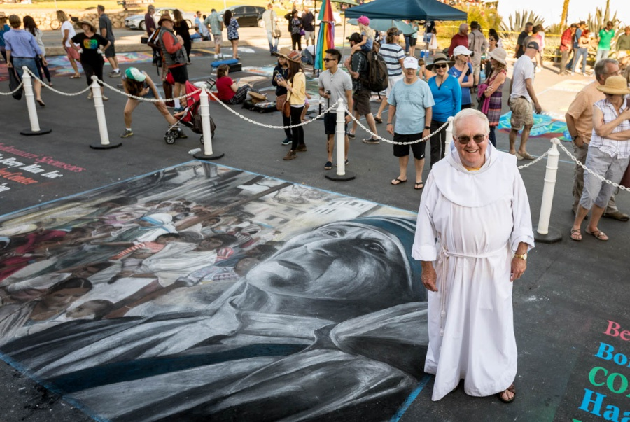 Father Larry Gosselin, rector of the Santa Barbara Mission, stands with Mother Teresa, who was declared a saint by the Catholic Church last year and was the featured chalk drawing at this year's I Madonnari.