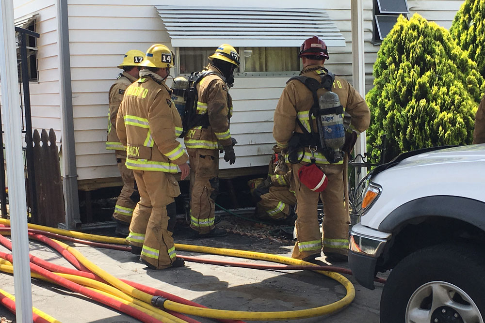 Firefighters dousing fire under mobile home.