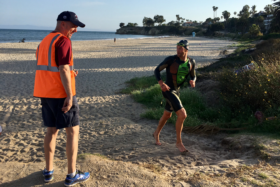 man finishes swim and runs across beach