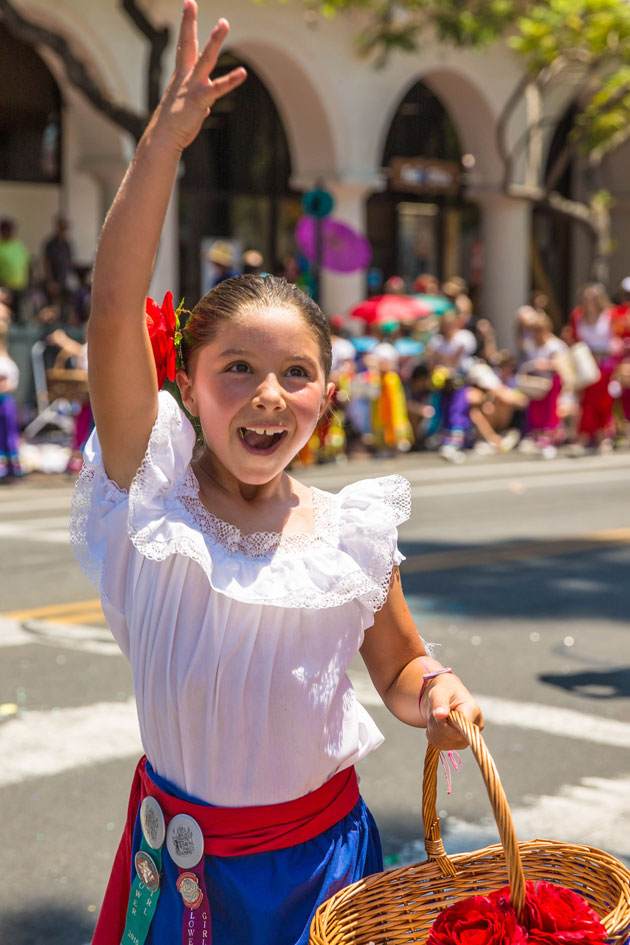 A Fiesta flower girl tosses brightly colored roses and daisies into the crowd along State Street during the parade.