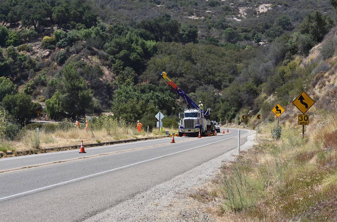 A crane gets set to haul up a pickup truck that plunged over the side of Highway 154 at Windy Gap on Aug. 6.