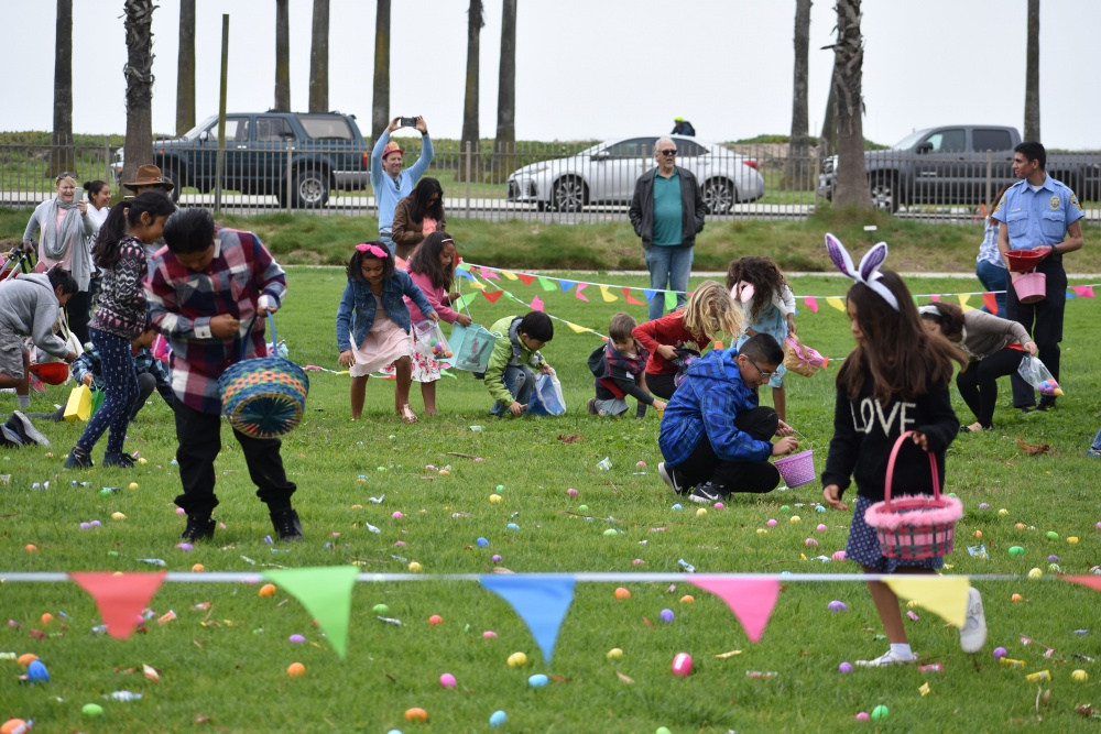 Children with Easter baskets pick up Easter eggs in a field, watched by parents and officials.